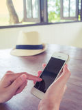 Human hand holding smartphone on wooden table Stock Image