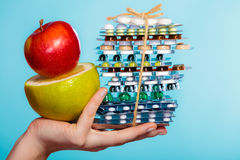 Human hand holding stack of pills and fruits on blue. Stock Image