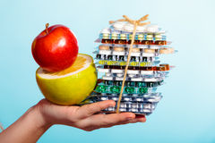 Human hand holding stack of pills and fruits on blue. Royalty Free Stock Images