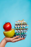 Human hand holding stack of pills and fruits on blue. Royalty Free Stock Photo