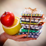 Human hand holding stack of pills and fruits Royalty Free Stock Photo