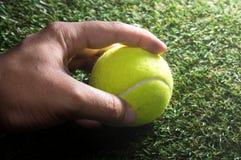 Human hand holding tennis ball. Royalty Free Stock Photo