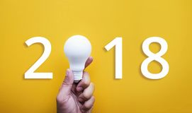 2018 Ideas creativity concept with human hand holding light bulb. Human hand holding white lightbulb on pastel color background.Ideas creativity,inspiration Stock Image