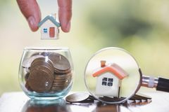 The human hand holds the house on the coin, planning savings money of coins to buy a home concept, mortgage and real estate stock photography
