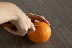 Human hand holds knife and cuts orange on wooden table royalty free stock photo