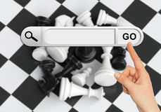 Human hand indicates the search bar in browser. Chess pieces and chessboard on background Royalty Free Stock Images