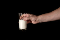 Human hand keeps the glass with milk. On a black background Royalty Free Stock Images