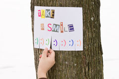 Human hand keeps for paper ad with the phrase: Take a Smile and with smile signs. The photo is on a tree Stock Photos