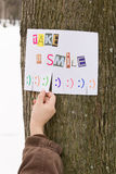 Human hand keeps for paper ad with the phrase: Take a Smile and with smile signs ready to be tore off. Stock Images