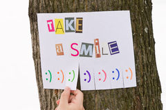 Human hand keeps for paper ad with the phrase: Take a Smile and with smile signs ready to be tore off. The photo is on a tree stock photography