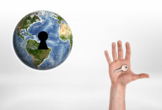Human hand with the key from planet Earth. Royalty Free Stock Images