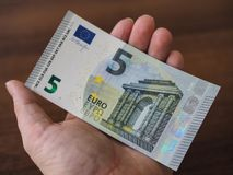 On the human hand lies a beautiful new bill 5 Euro. Close-up, blur royalty free stock images