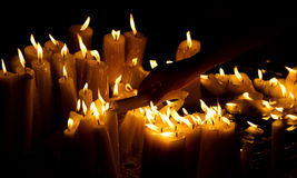 Human hand lighting candle in church Stock Images