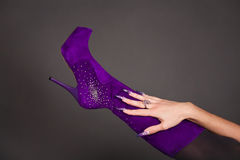 Human hand with manicure touch purple boot Stock Photos