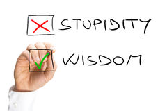 Human Hand Marking X on Stupidity and Check on Wisdom Stock Image
