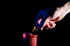 Human hand with a match lights a red candle Royalty Free Stock Image