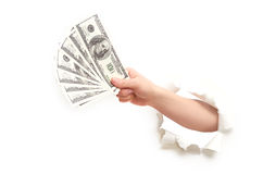 Human hand with money American dollars through  hole in  white paper Stock Photography