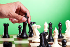 Human hand moves king on chessboard Stock Photos