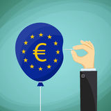 Human hand with a needle and a balloon with the flag of the Euro Royalty Free Stock Photography