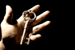 Human hand with an old key. Isolated on black background Royalty Free Stock Images