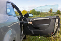 Human hand opens the car door In the countryside Royalty Free Stock Photography