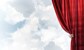 Cloudy landscape behind red curtain and hand holding it. Human hand opens red velvet curtain on blue sky background royalty free stock image
