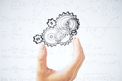 Human hand and painted gears at equations background Stock Photos