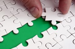 The human hand paves the way to the surface of the jigsaw puzzle, forming a green space. The concept of overcoming the difficultie. S on the way to success Royalty Free Stock Images