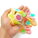 Human hand pick up jelly sweet candy isolated on white Stock Image