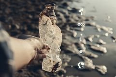 Human hand picking up bottle plastic with icon on crack ground beside the lake outdoor on the baking hot day. Drought and environmental problems royalty free stock images