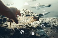 Human hand picking up bottle plastic with icon on crack ground beside the lake outdoor on the baking hot day. Drought and environmental problems royalty free stock photos