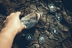 Human hand picking up bottle plastic with icon on crack ground beside the lake outdoor on the baking hot day. Drought and environmental problems stock photos