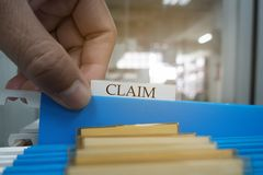 Hand is picking up the claim document in the file for the client to the insurance company.insurance concept. Human hand is picking up the claim document in the stock photos