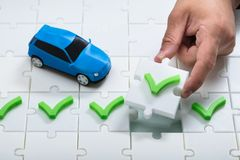 Human hand placing check mark icon puzzle. Near small blue car royalty free stock image