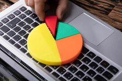 Human Hand Placing Last Piece Into Pie Chart. Close-up Of A Human Hand Placing Last Piece Into Pie Chart Over Laptop Keypad stock photo