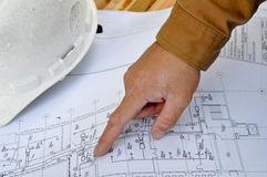 Human Hand Pointing at Plans. Human Hand Pointing at Construction Plans Royalty Free Stock Photos