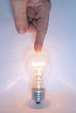 Human hand points a finger at the lamp Royalty Free Stock Photo