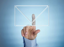Human hand pressing virtual mail icon. Male hand pressing mail icon on futuristic transparent display stock photo
