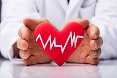 Human Hand Protecting Heart With Heartbeat. On White Background royalty free stock images