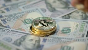 Human hand put gold bitcoin, dash and ethereum coins on dollar banknotes. World cryptocurrency business. Human hand put gold bitcoin, dash and ethereum coins on stock footage
