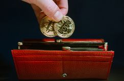 Human hand put in red long wallet two coins bitcoin gold color. Storage of funds Stock Photography