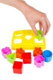 Human hand puts wrong shape into shape sorter toy isolated. Human hand puts wrong shape into shape sorter toy with various coloured blocks isolated on white stock photos