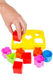 Human hand puts wrong shape into shape sorter toy isolated Stock Photos