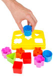 Human hand puts wrong shape into shape sorter toy isolated. Human hand puts wrong shape into shape sorter toy with various coloured blocks isolated on white royalty free stock images
