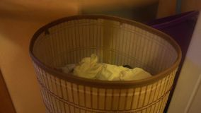 The human hand raises the lid of the basket for dirty Laundry and throws the dirty clothes.  stock footage