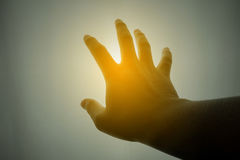 Human hand reaching for the sun. Silhouette Royalty Free Stock Images