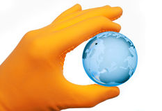 Human hand with rubber glove holding glass globe Royalty Free Stock Image