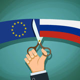 Human hand with scissors cuts the flag of Russian and the Europe Royalty Free Stock Image