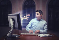 Human hand from the screen. Scaring a young businessman Stock Images