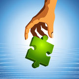 Human hand shining piece of puzzle. Human hand with a green shining piece of puzzle Stock Photos